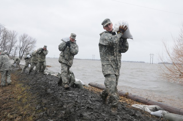From right to left, Spcs. Eric Wiederholt, Joshua Lanzdorf and Randy Birchfield of the 815th Engineer Company based in Lisbon, N.D., carry sandbags in the rain, along a flood levee for placement in a flood barrier April 10 at a rural farmstead in Cass County, N.D.