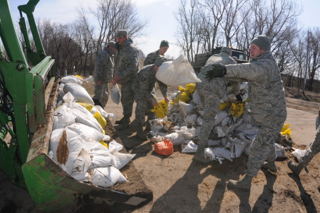 Master Sgt. David Bush, of the 119th Civil Engineer Squadron, right, is one of several members of a North Dakota National Guard quick response force (QRF) team throwing sandbags into the bucket on a farm tractor April 12, near Enderlin, N.D.