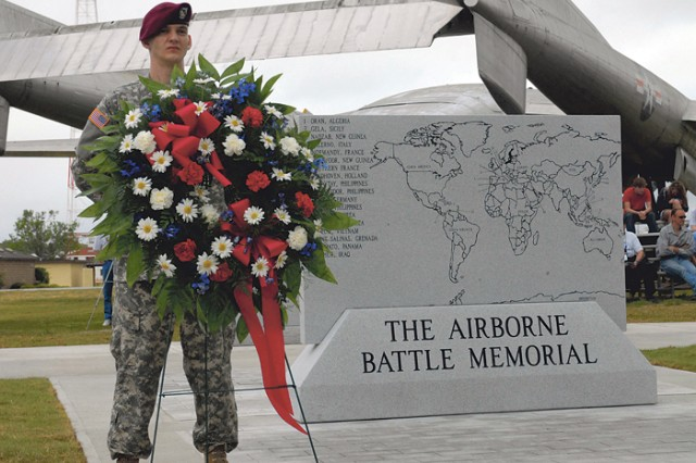 Pfc. Ryan Smith of 1st Battalion (Airborne), 507th Parachute Infantry Regiment stands next to the Airborne Battle Memorial marker. The new $112,000 monument opened Friday at Eubanks Field.