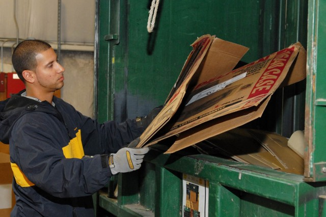Jason Sabater, recycling employee, loads scrap cardboard into a baler for recycling at Tobyhanna Army Depot.