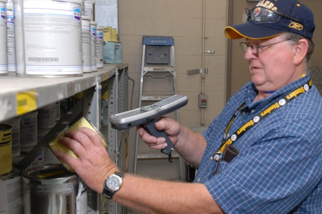 Ed VanCamp, painter helper, scans a can of paint into the Hazardous Material Management System at Tobyhanna Army Depot.