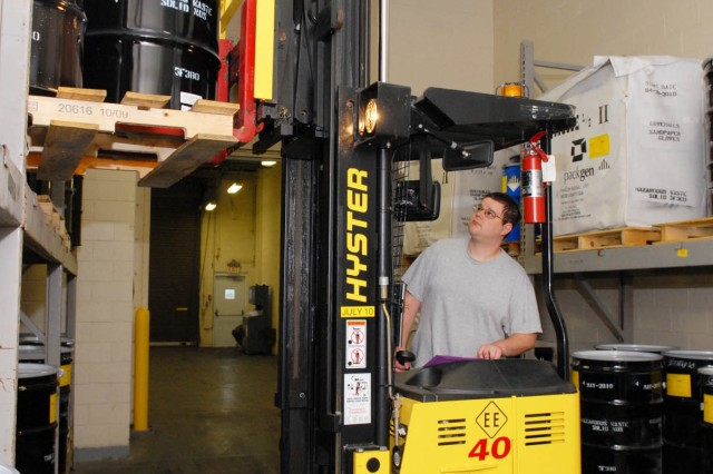 Matt Argust, environmental protection specialist, places hazardous waste on a storage rack to await shipping off Tobyhanna Army Depot.