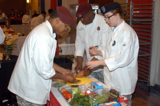 "Sgt. Andre Nash, Sgt. 1st Class Oscar Smith and Spc. Amanda Liesse, a combined team of Connelly Award winners, prepare ingredients for the Magnificent Mile Bistro Challenge April 1. Five teams competed head-to-head during the 90-minute ""Iron Chef""-style competition that required quick thinking and planning when coconut was added to the menu as the mystery ingredient.  (U.S. Army photo by Keith Desbois)"