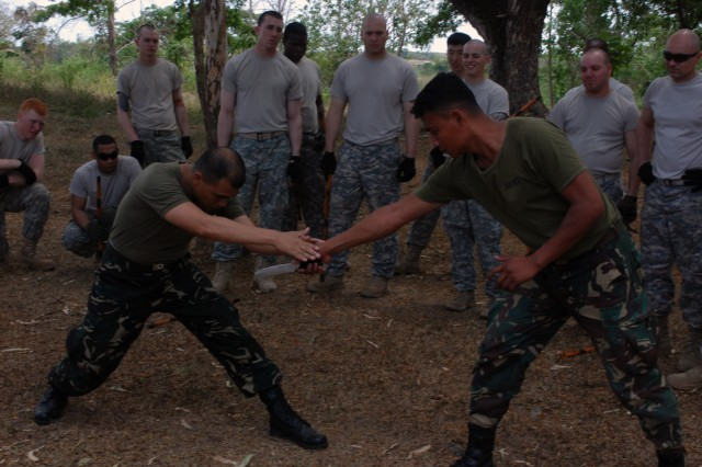 Maj. Danilo Estrañero (left), Armed Forces of the Philippines, demonstrates how to defend against a knife-wielding opponent to U.S. Army Soldiers during hand-to-hand combat training at Fort Magsaysay, Philippines, April 7. The training was part of Exercise Balikatan 2011, an annual joint exercise between the armed forces of the U.S. and the AFP.