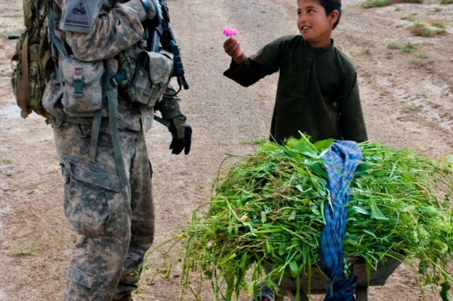 An afghan child offers a flower to U.S. Army Sgt. John M. Davis, a team leader for 3rd Platoon, Mad Dog Troop, 4th Squadron, 2nd Stryker Cavalry Regiment from Vilseck, Germany, during a patrol near Kandahar Airfield, Afghanistan, April 14, 2011. Davis, a Pocatello, Idaho, native, has a working proficiency of Pashto, one of the main languages in Afghanistan, and often speaks with children during patrols. (U.S. Army photo by Spc. Edward A. Garibay, 16th Mobile Public Affairs Detachment)