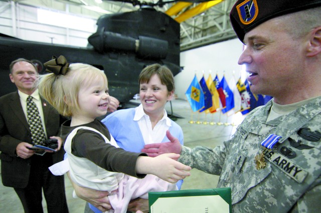 Olivia Litaker, 6, gives her daddy, CW4 Bunky Litaker, a hug following the Distinguished Flying Cross medal ceremony.
