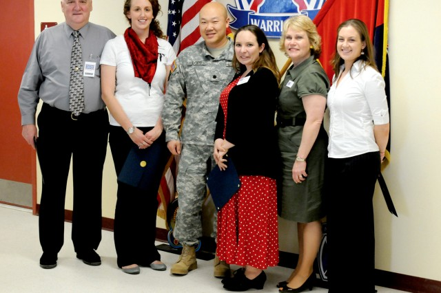 Lt. Col. Michael Loos, 2nd Battalion, 22nd Infantry Regiment commander, center, stands with several USO volunteers and staff after thanking them for supporting 1st Brigade Combat Team during its recent redeployment from Afghanistan. From left are George Barton, Kyra Waterson, Loos, Melissa Amos, Karen Clark and Allie May.