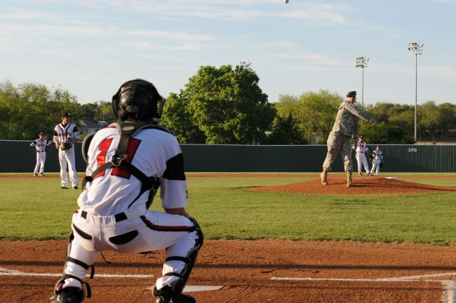 """HARKER HEIGHTS, Texas- Lt. Col. Mark Davey (center), commander of the 2nd Special Troops Battalion, 2nd Brigade Combat Team, 1st Cavalry Division, throws out the first pitch during the Harker Heights """"Knights"""" High School varsity baseball game against the Temple """"Wildcats"""" April 12.  The 2nd STB sponsors the HHHS and is generously involved with its JROTC program."""