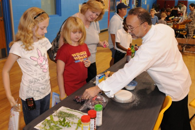 Eduardo Renta, chef and military spouse, discusses the calorie content of certain foods with Cindy Crawford, military spouse, and her daughters, Summer, 10, and Isabella, 8, during the annual Health and Nutrition Fair at the CYSS gym April 6.