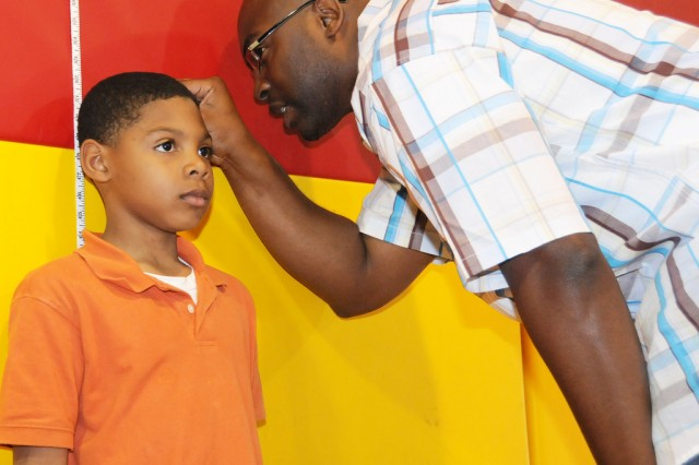 Leroy Minus, youth sports assistant director, measures Traelon Thornton's height.
