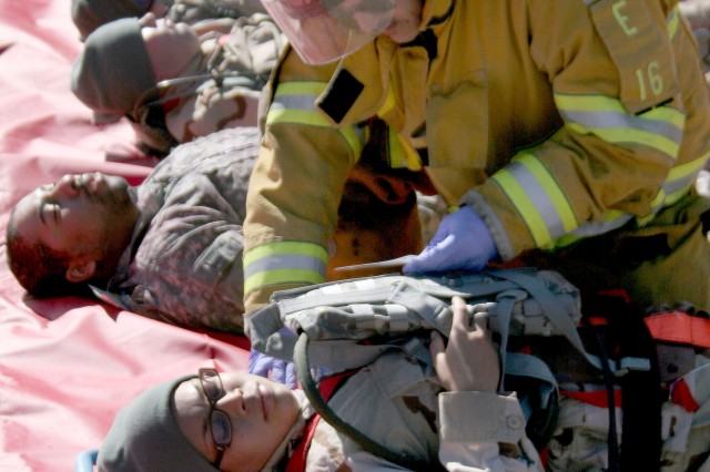 """FORT CARSON, Colo. -- Colorado Springs firefighter Jeff Martin treats Pvt. Melissa Reznick-Chech, 4th Engineer Battalion, for an """"abdominal wound."""" Soldiers were made-up to portray victims for the """"Mountain Thunder"""" exercise."""