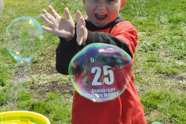Justin Lewis, 6, tries to catch bubbles coming out of bubble machines during Fort Irwin's Children's Fitness Fair and Presidential Fitness Challenge April 9 at Army Field.
