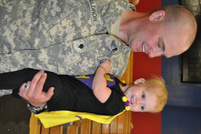 """One-year-old Celia Waldron dances with her dad, Spc. Michael Waldron, 2nd Squadron, 11th Armored Cavalry Regiment, during Baby Loves Disco at Fort Irwin's Freedom Fitness Center April 5.  Celia wore a homemade costume with a cape proclaiming her """"Super Celia."""""""