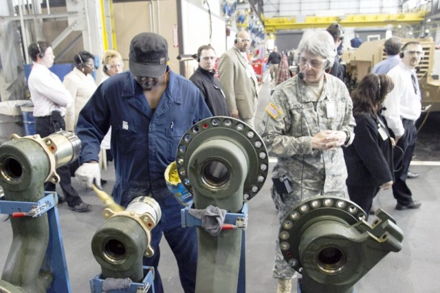 Anniston Army Depot mechanic William Threatt greases road arms for an M1 tank in the Combat Vehicle Repair Facility as Col. Joanne Hooper and other members of the TACOM Life Cycle Management Command inspection team look on.