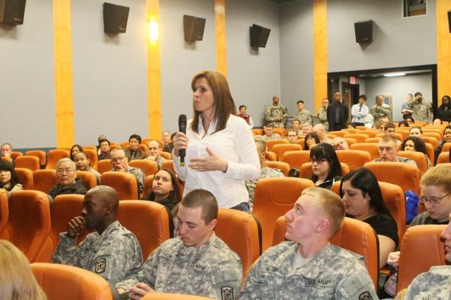 Sue Durham, spouse of Lt. Col. Christopher Durham, Division Special Troops Battalion commander, asks a question during the U.S. Army Garrison Red Cloud and Area I town hall meeting in the Camp Red Cloud Theater April 5.
