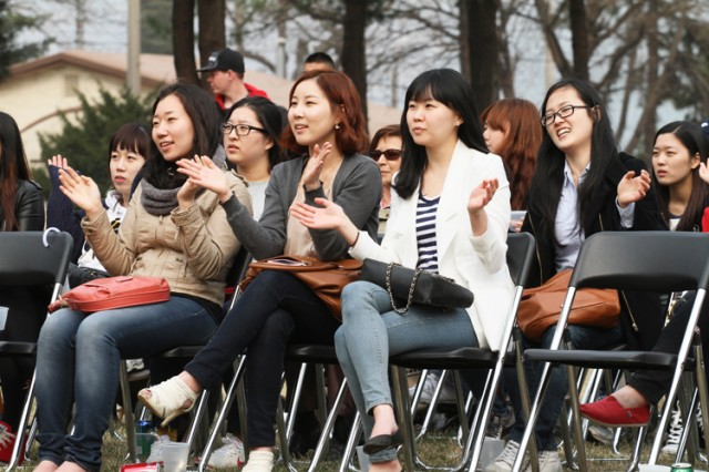 CAMP RED CLOUD, South Korea - Korean guests, who were granted access to the installation here for the concert, clap to the music showing their approval of the entertainment provided by the 2nd Infantry Division and 26th Mechanized Infantry Division bands during the Concert on the Village Green.