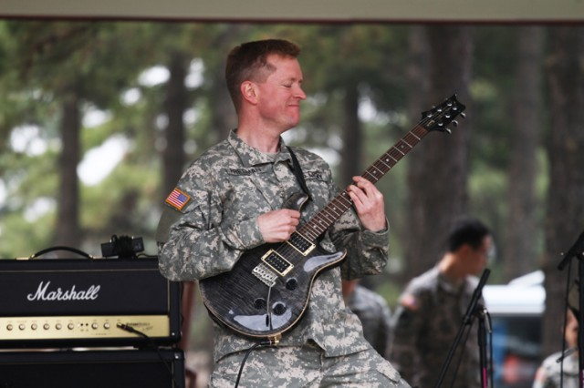 """CAMP RED CLOUD, South Korea - Staff Sgt. Charles Freeman from the 2nd Infantry Division Band here jams to a rock version of """"Arirang"""" - the much beloved Korean folk song - during a Concert on the Village Green here April 10."""