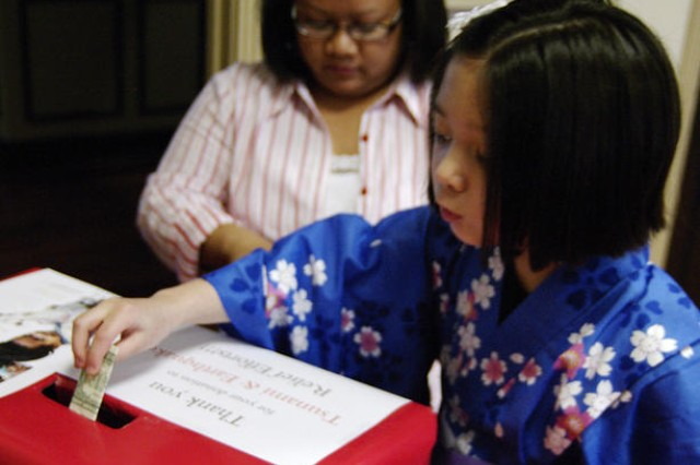 Payton Armstrong, 8, a third-grader at West Meade Elementary School, makes a donation with her mother, Gena, for the victims of Japan's March 11 earthquake and tsunami. The Armstrongs were among the 20 people who attended the fundraiser Sunday at Heritage Park Neighborhood Center.