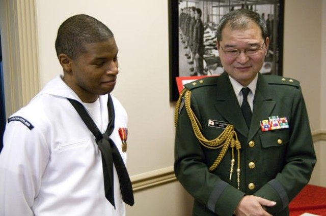 Navy Petty Officer 2nd Class Keith Hudson discusses Japan's recent earthquake and tsunami with Maj. Gen. Mitsuru Nodomi, defense and military attaché to the United States from the Japanese Embassy. Nodomi was a guest speaker Sunday afternoon at a fundraiser organized by Hudson's wife, Caress.