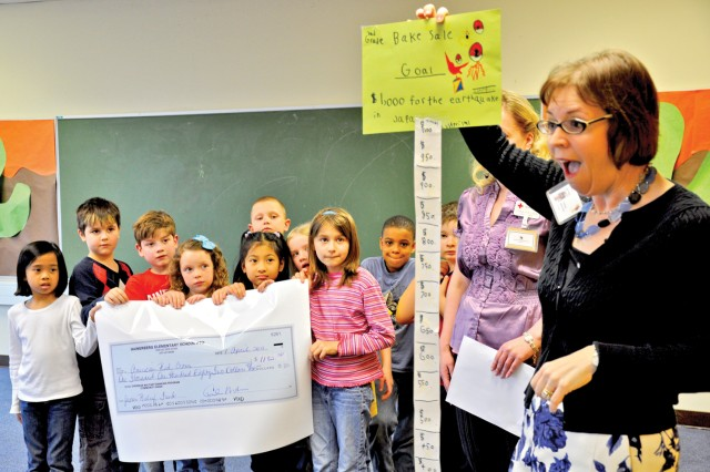Hainerberg Elementary School Principal Penelope Miller-Smith congratulates Hainerberg Elementary School second-graders for their efforts in raising $1,182.50 through an April 1 bake sale to benefit the American Red Cross relief efforts for victims of the earthquake and tsunami in Japan.