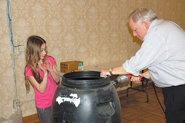 """Bill Frye, an Alexandria, Va., resident drills a hole to insert the spout in one of his three assembled barrels at the DEM-sponsored rain barrel workshop at JBM-HH March 31 while his 10-year-old daughter Isabel, supervises. Frye said his wife found out about do-it-yourself rain barrels last year, assembling one at a workshop she attended with their daughter and a German exchange student they hosted. ''The girls painted the barrel, including flowers,"""" said Frye. ''Rain barrels are good for the environment,"""" said Isabel, who plans to paint the barrels the Frye Family assembled at JBM-HH to collect water from down spouts at each corner of their home."""