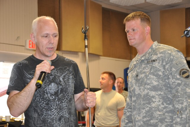 Lang Bliss, a live music producer for Tom Jackson Productions, explains to The Army Ground Forces Band's Brass Brigade vocalist Staff Sgt. Tanner how to properly use the microphone stand while performing.