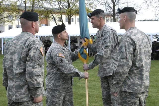 Command Sgt. Maj. Darieus A. ZaGara passes on the colors as Command Sgt. Maj. Dennis C. Zavodsky (far right) prepares to receive them here April 14 in a Change of Responsibility Ceremony.  The ceremony was to honor ZaGara, after serving as CSM for Joint Multinational Training Command. Zavodsky, former Command Sgt. Maj. for the 25th Infantry Division's 4th Brigade Combat Team, will replace ZaGara as Command Sgt. Maj. for Joint Multinational Training Command.