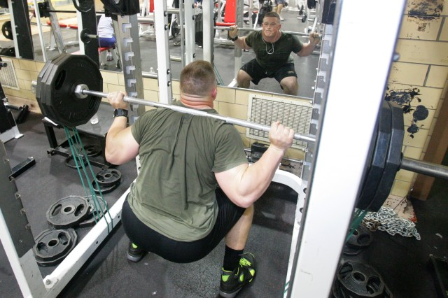 1st Lt. Collin Mooney does some squats at Honeycutt Fitness Center at Fort Sill, Okla. At each end of the barbell Mooney attached rubber bands which increase the resistance adding about 40-50 pounds to the lift. The bands help create explosiveness and power.