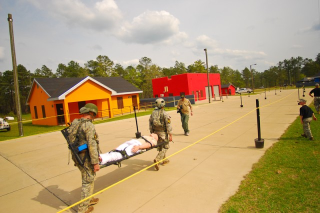 2011 Best Ranger Competition competitors conduct a litter carry during the Urban Operations portion of the competition.