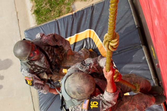 2011 Best Ranger Competition competitors climb up a rope during the Urban Operations event.