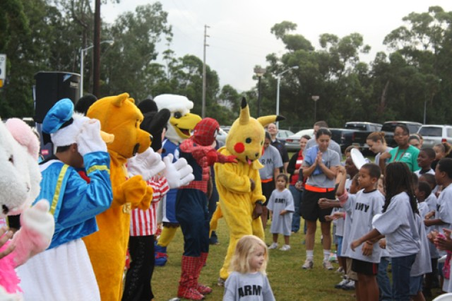 "SCHOFIELD BARRACKS, Hawaii -- Army keiki and parents play and dance with DFMWR's CYSS staff, disguised as Donald Duck, Winnie the Pooh, Mickey Mouse, Eddie the Eagle, Spiderman and Pikachu, during ""PT in the Park,"" April 5."