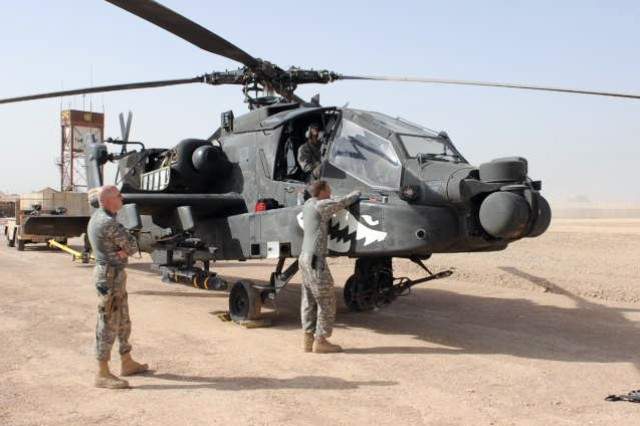 """BABIL, Iraq - Soldiers of Company B, 1st Battalion, 229th Aviation Regiment, 21st Cavalry Brigade, perform maintenance checks on an AH-64D Apache helicopter before a mission out of Contingency Operating Site Kalsu April 12, 2011. The """"Tigersharks"""" of Company B are conducting counter indirect-fire missions and supporting ground convoys for the 3rd Armored Cavalry Regiment. US Army photo by Staff Sgt. Garrett Ralston (110412-A-8856R-022)"""