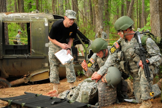 """Capt. Jonathan Norton, right, and Capt. Randal Waters, both of 4th Ranger Training Brigade, administer aid to a """"casualty"""" during Ranger day stakes April 16 during the 2011 Best Ranger Competition at Fort Benning, Ga."""