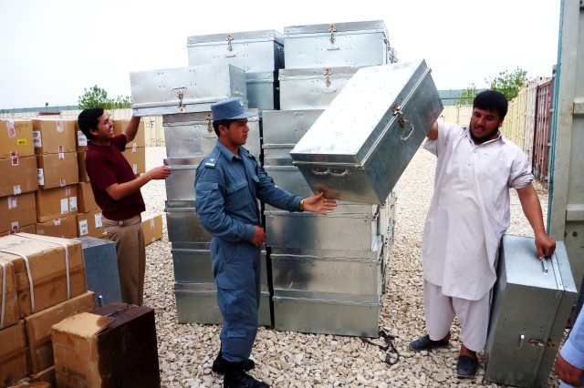 """Afghan personnel at the Regional Training Center-Konduz transport metal footlockers for the """"expansion"""" training area into a nearby conex. The expansion area will open in May and allow another 400 student to train as Afghan National Civil Order"""