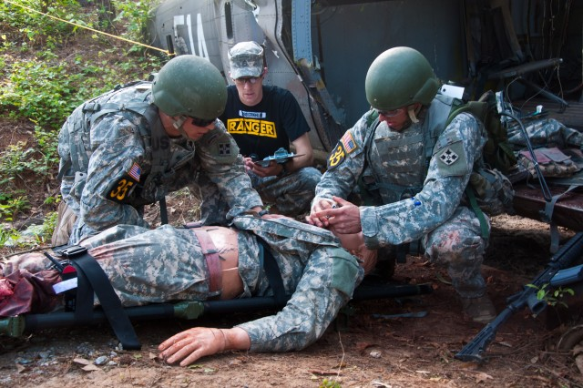 1st Lt. Kevin Werner and Capt. George Rhynedance from the 4th Infantry Division, rescue a simulated casualty at a downed aircraft on the Ranger First Responder event during day 2 of the Best Ranger Competition at Todd Field, Fort Benning, Ga. During the teams's assessment of the simulated casualty, a Ranger medic grades the level of care performed by the competitors.