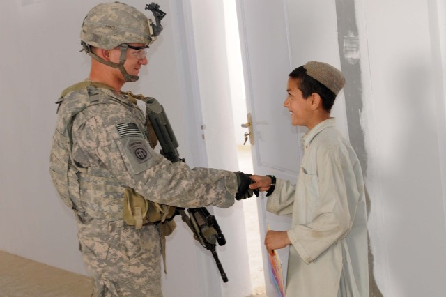 WEESH, Afghanistan - 1st Lt. Andrew Beckwith, Personal Security Detachment platoon leader, Headquarters and Headquarters Company, 525th Battlefield Surveillance Brigade, and Falls Church, Va., native, shakes hands with an Afghan student at the newly constructed Weesh school for boys near the Afghanistan-Pakistan border, March 31, 2011. (Army Photo by Spc. Jonathan W. Thomas, 16th Mobile Public Affairs Detachment)