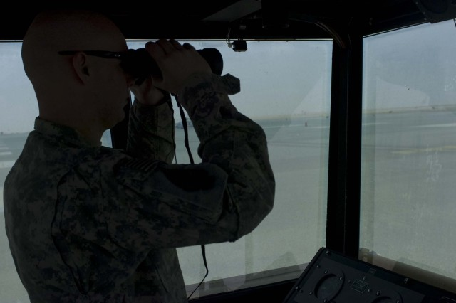 """TAOG Ends Mission  CAMP ARIFJAN, Kuwait --Pfc. Mathew Miller, an air-traffic control operator with 1st Battalion, 58th Airfield Operation Battalion, 164th Theater Aviation Operation Group and native of Middleville, Mich., watches for incoming aircraft from his perch in the group's mobile air-traffic control tower Apr.14 at Udairi Army Airfield, Camp Buehring, Kuwait.  According to the group's commander, Col. James R. Macklin, Jr., his Soldier's hard work and dedication """"made the mission possible.""""  (U.S. Army photo by Sgt. M. Benjamin Gable, 27th Public Affairs Detachment) - 30 -"""