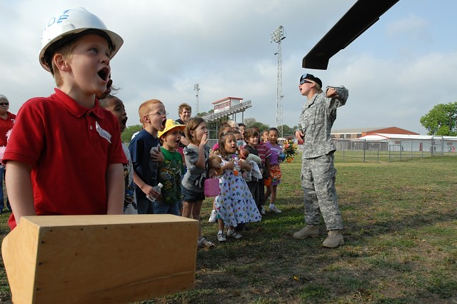 FORT HOOD, Texas-Spc. Melissa Platt (right), a motor pool dispatcher with Company E, Task Force Spearhead, 1st Air Cavalry Brigade, 1st Cavalry Division, from Wausau, Wis., gives a briefing to students from Tyler Elementary School in Belton, Texas during the school's career day activities, April 8.
