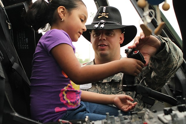 FORT HOOD, Texas-Chief Warrant Officer 2 Bryan Lee, a pilot with Company C, Task Force Spearhead, 1st Air Cavalry Brigade, 1st Cavalry Division, from Plugerville, Texas, explains the functions of a cyclic stick on a UH-60A Black Hawk helicopter to a student from Tyler Elementary School in Belton, Texas, April 8. Tyler Elementary is one of the task force's adopted school and the Soldiers from TF Spearhead took part in the school's career day