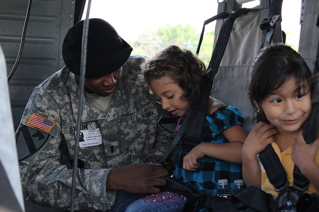 FORT HOOD, Texas-1st Lt. Lakito Bynum, a maintenance platoon leader for Company E, Task Force Spearhead, 1st Air Cavalry Brigade, 1st Cavalry Division, originally from Charleston, Miss., buckles in a student  inside of a UH-60A Black Hawk helicopter, April 8. The student, along with her fellow classmates from Tyler Elementary School in Belton, Texas, had the chance to interact with pilots and crew chiefs and learn about Army aviation during the school's career day activities.