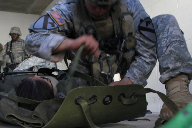 FORT HOOD, Texas-A flight medic from Company C, Task Force Lobos, 1st Air Cavalry Brigade, 1st Cavalry Division, prepares a 'casualty' for evacuation during a mass casualty exercise here, April 9. The exercise put all of the flight medics from Co. C through different scenarios in which they had to test their tactical skills along with their ability to conduct on-the-spot medical care and transport casualties via air medical evacuation.