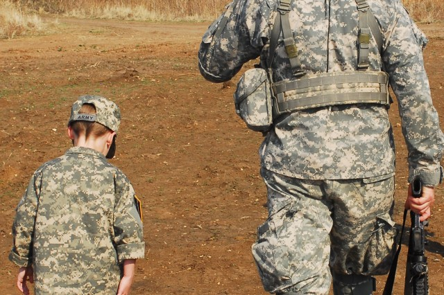 """Ian Field, 7, joins his squad leader, 1st Sgt. Brandon McGuire, as they make their way back to their Humvee following a """"battle"""" on the expert infantryman badge course."""