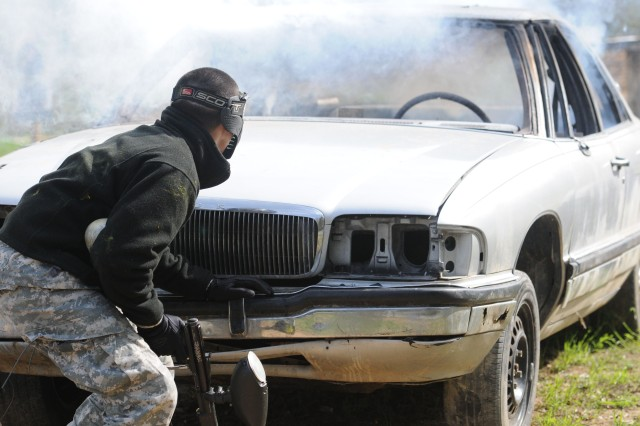 Private 1st Class Jose Valentin, an Intel analyst with the 3d ESC, uses an exploded car as cover during training at Burcham Urban Assault Course. During the course, Soldiers were often surprised by simulated explosives and booby traps. (U.S. Army photo by Sgt. Michael Behlin)