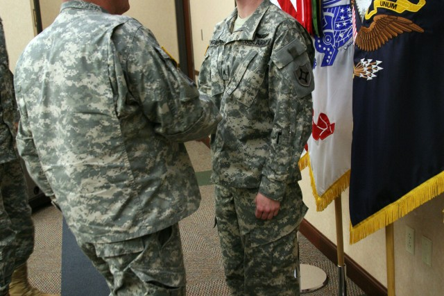Sgt. Alisha McRoberts, a Wounded Warrior assigned as a management analyst in the U.S. Army Space and Missile Defense Command/Army Forces Strategic Command G-3 office, accepts a coin from Lt. Gen. Richard P. Formica, commanding general, USASMDC/ARSTRAT, following McRoberts reenlistment ceremony April 15 in the command's headquarters on Redstone Arsenal.