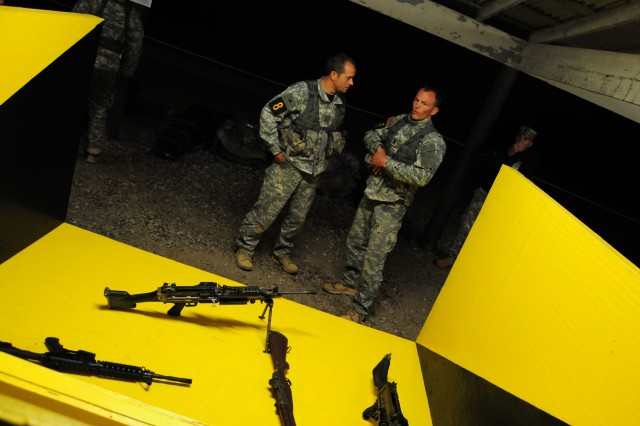 Master Sgt. Eric Turk, left, and Sgt. Maj. Walter Zajkowski, complete assembling weapons during Ranger night stakes at 2 a.m. on April 17. Zajkowski won Best Ranger in 2007 and Turk won in 2010.