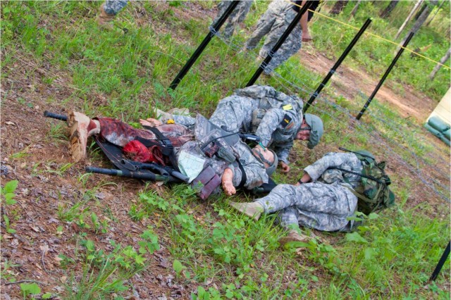 Capt. Nathan Lokker and Sgt. 1st Class Conrad Kaluzny drag their fallen 'Soldier' through barbed wire during the 2011 Best Ranger Competition at Fort Benning, Ga.
