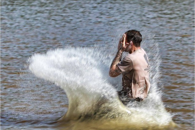A competitor drops into Victory Pond after completing the Water Confidence Test.