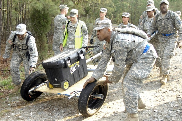 Second lieutenants Marlon Lynch, front left, and Sterling Griffin, front right, try to keep the wheels straight as their squad moves out with its makeshift cart during the April 15 Regimental Induction Challenge at Fort Lee, Va.