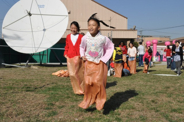 Children from the House of Dreams Orphanage participated in a potato sack race during the Easter Adventure hosted by the 6-52nd Air Defense Artillery at Suwon Air Base.