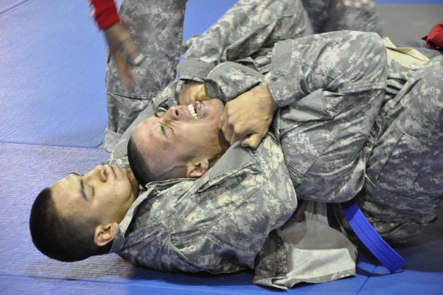 Alex Rodriguez (top), 302nd Brigade Support Battalion, is choked by Christian Gomez (bottom), 501st Special Troops Battalion during the Area IV Better Opportunities for Single and Unaccompanied Soldiers  Combatives Tournament at Camp Carroll, South Korea Apr. 16.